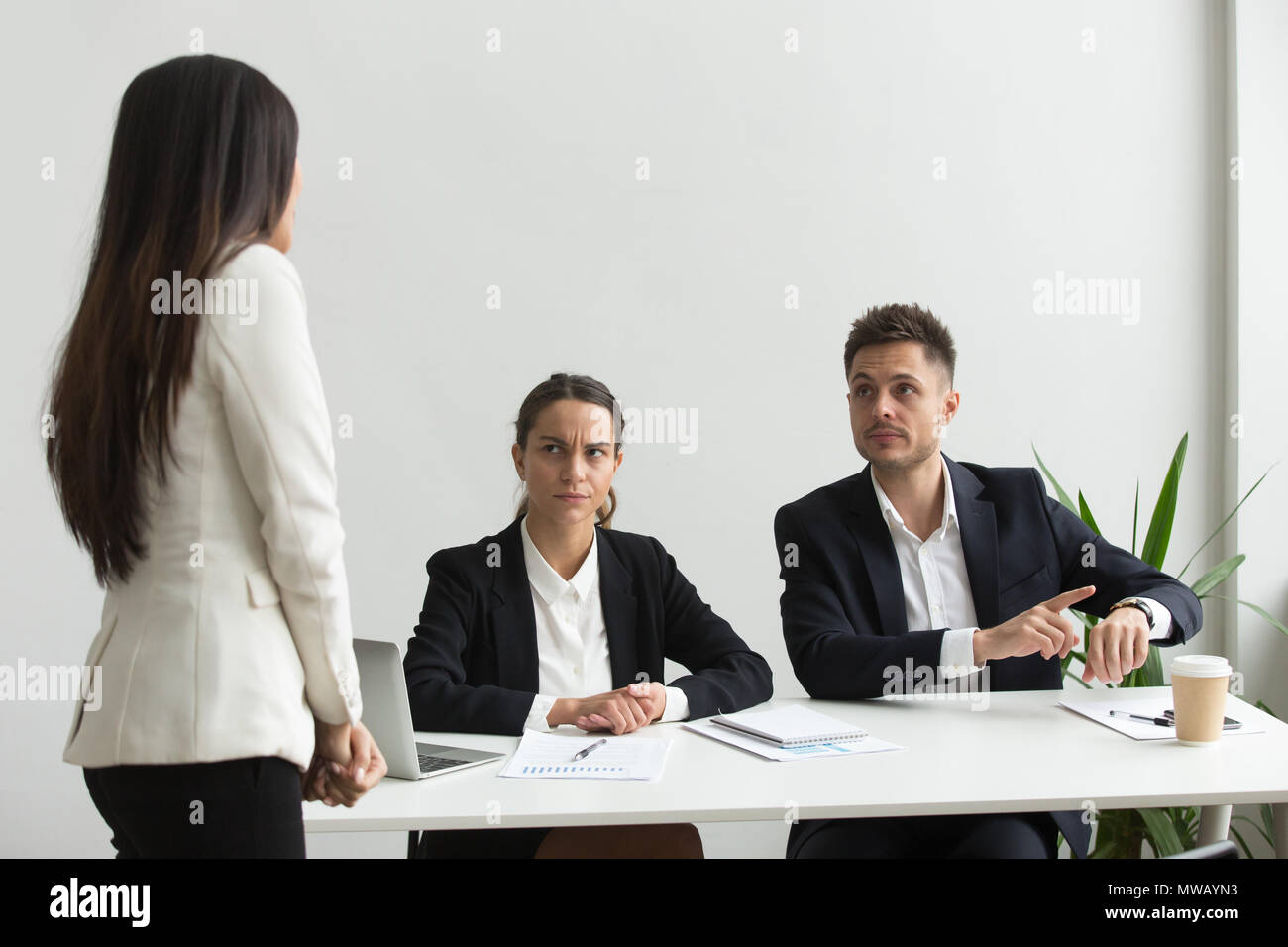 Angry executive pointing at wristwatch scolding employee for bei - Stock Image