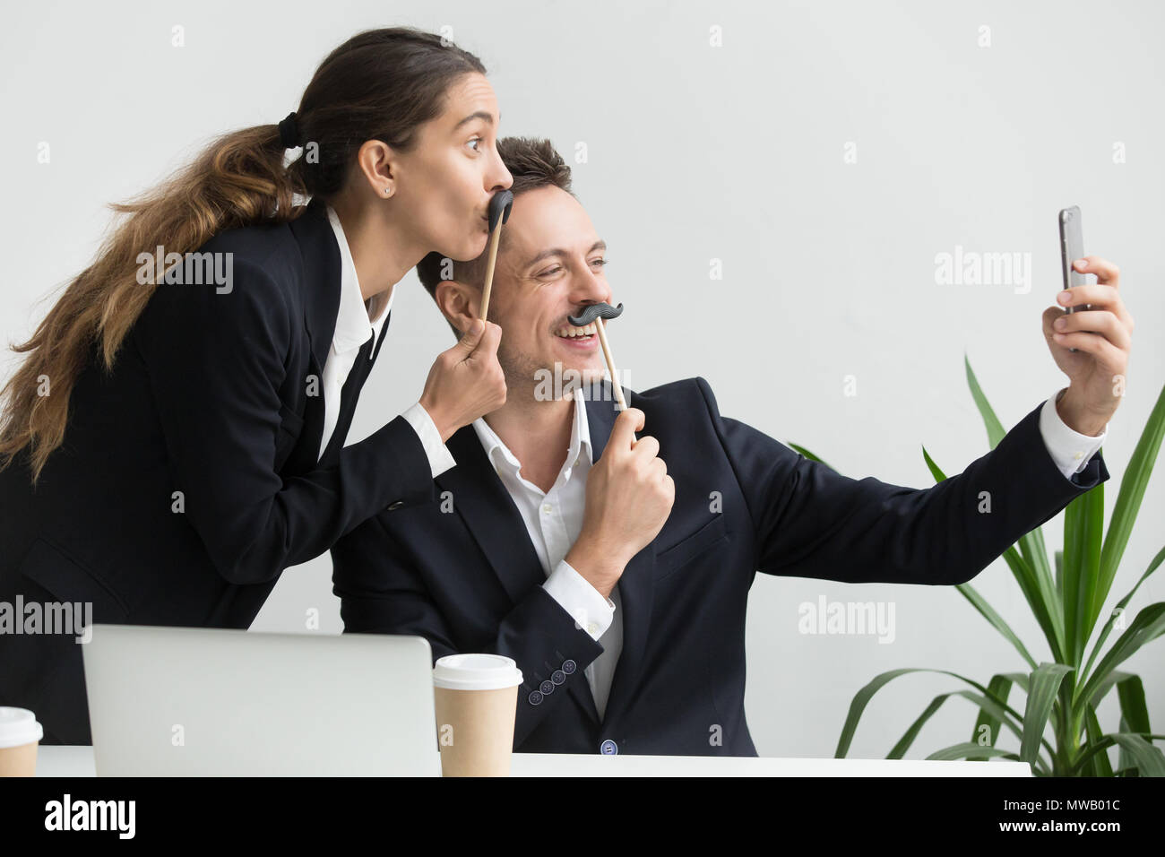 Friendly colleagues grimacing holding fake mustache taking selfi - Stock Image
