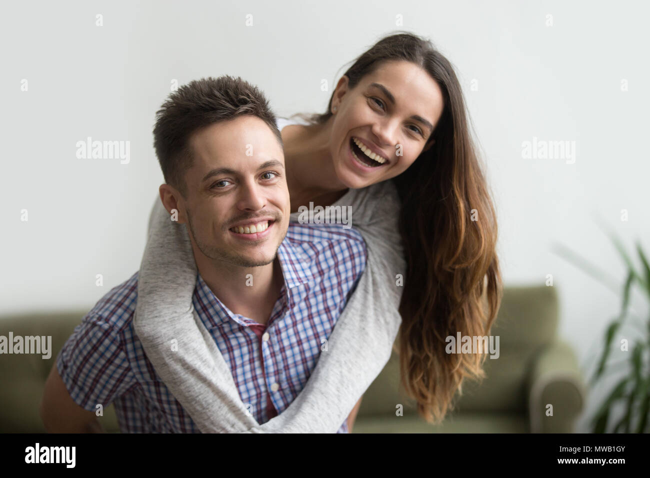 Smiling husband piggybacking cheerful wife at home, happy couple - Stock Image