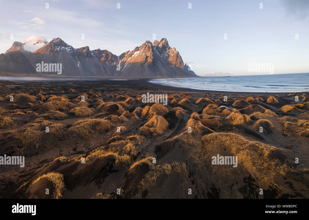 Black sandy beach, overgrown stones, mountains Klifatindur, Eystrahorn and Kambhorn, headland Stokksnes, massif Klifatindur Stock Photo