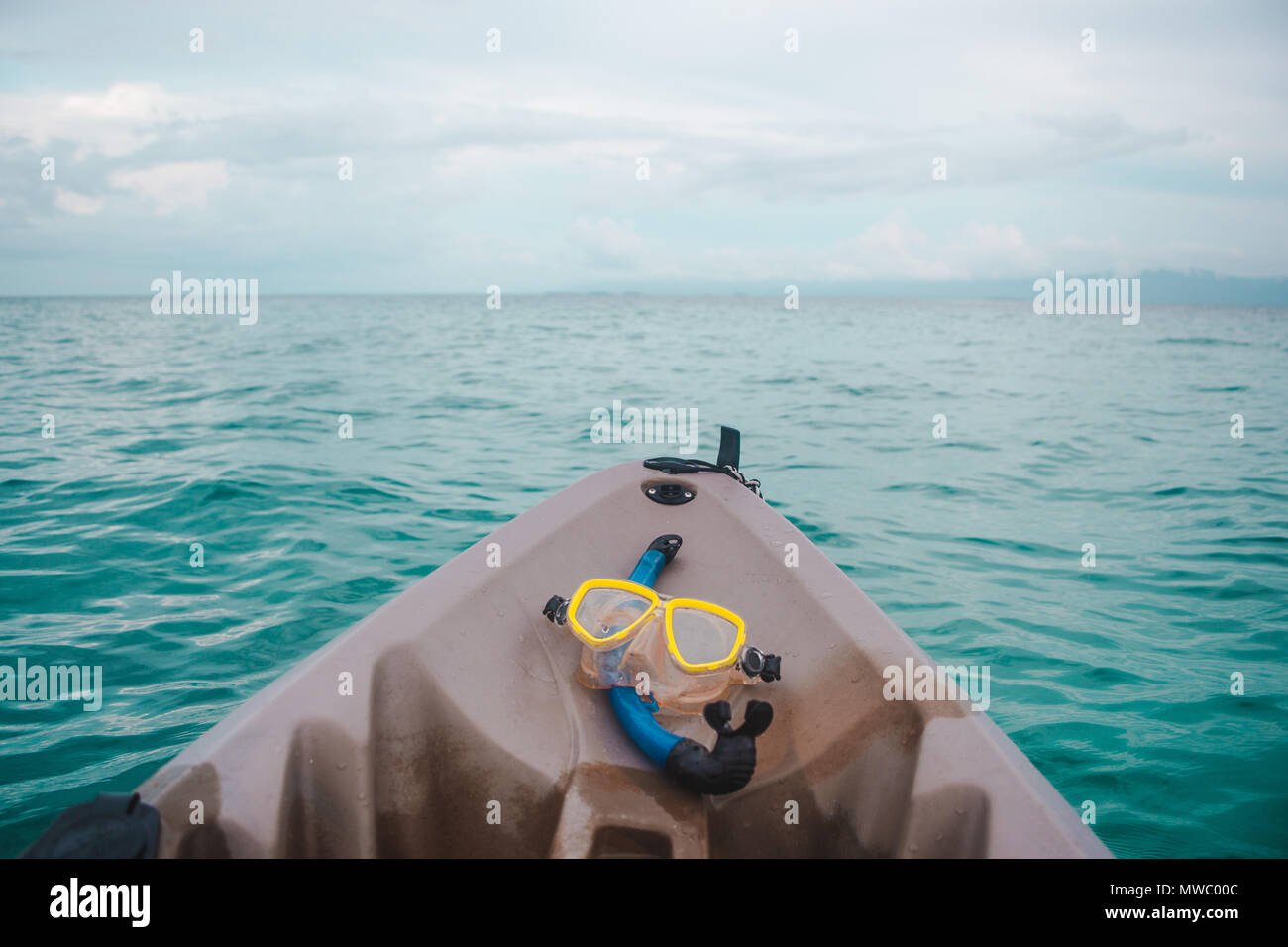 Blue snorkel and yellow goggles on the front of a brown plastic kayak in the turquoise water of the Caribbean Sea off the San Blas Islands, Panama - Stock Image