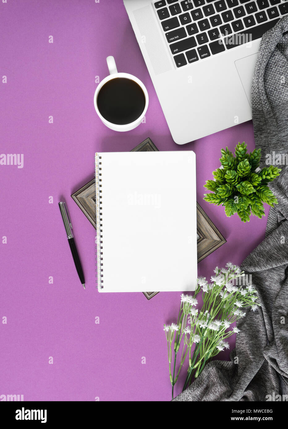 Home work space with notebook, laptop and coffee on pastel violet background. Home office flat lay top view. Stock Photo