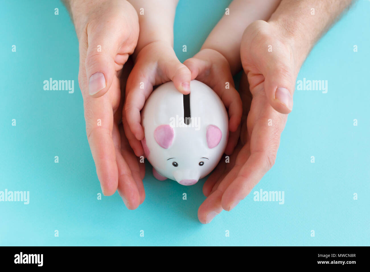 Family holding piggybank in hands. Investment concept - Stock Image