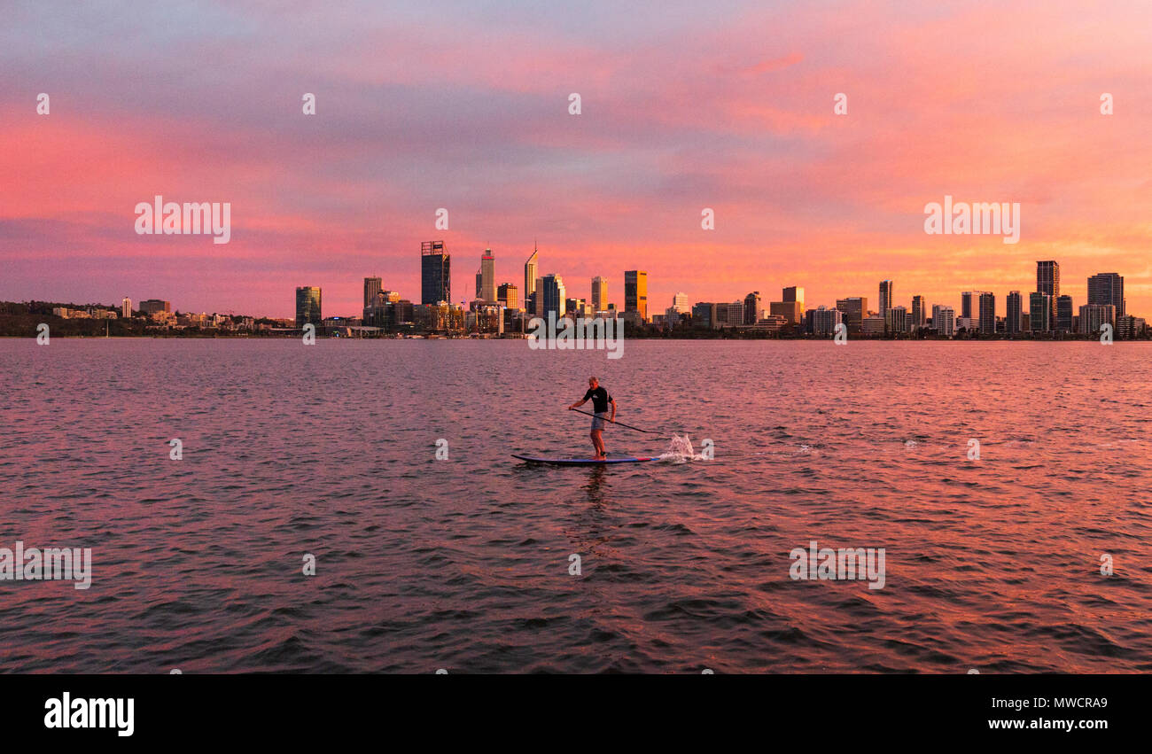 A man stand up paddleoarding on the Swan River with Perth city in the distance. Western Australia - Stock Image
