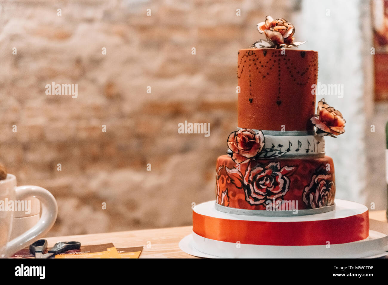 Wedding in the style of rock. Rocker or Biker wedding. Guys with stylish leather jackets. It's a rock'n'roll baby A sweet couple is cutting a wedding  - Stock Image