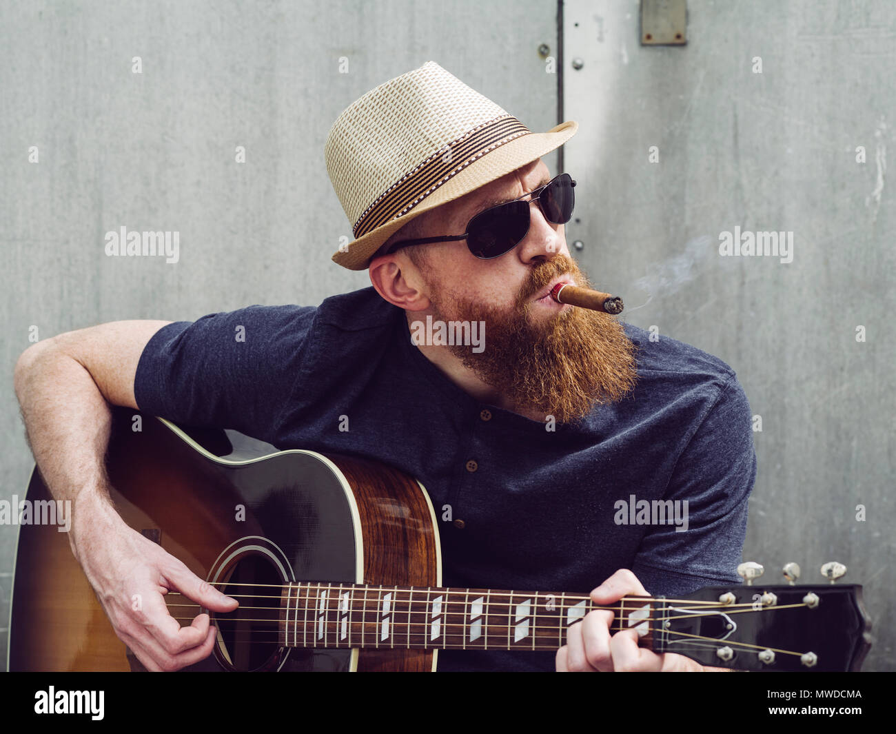 Photo of a bearded man playing acoustic guitar white smoking a cigar. - Stock Image