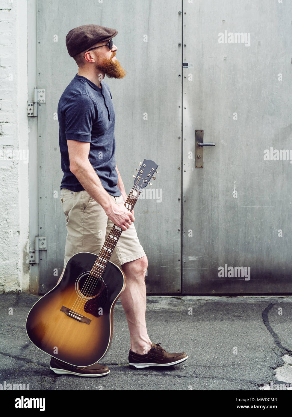 Photo of a bearded man walking with an acoustic guitar. - Stock Image