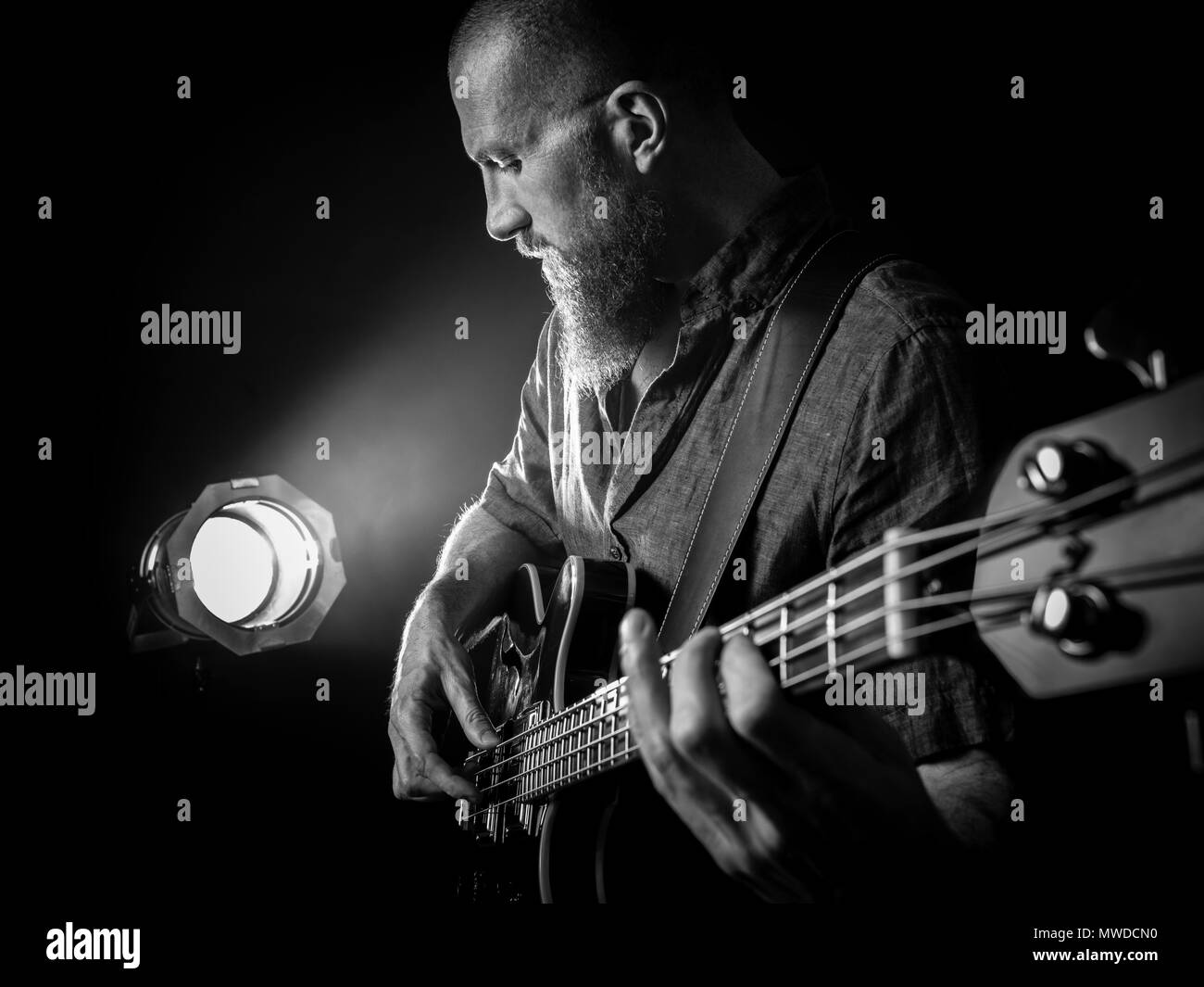 Photo of a bearded man playing bass guitar on stage in front of spotlights. - Stock Image