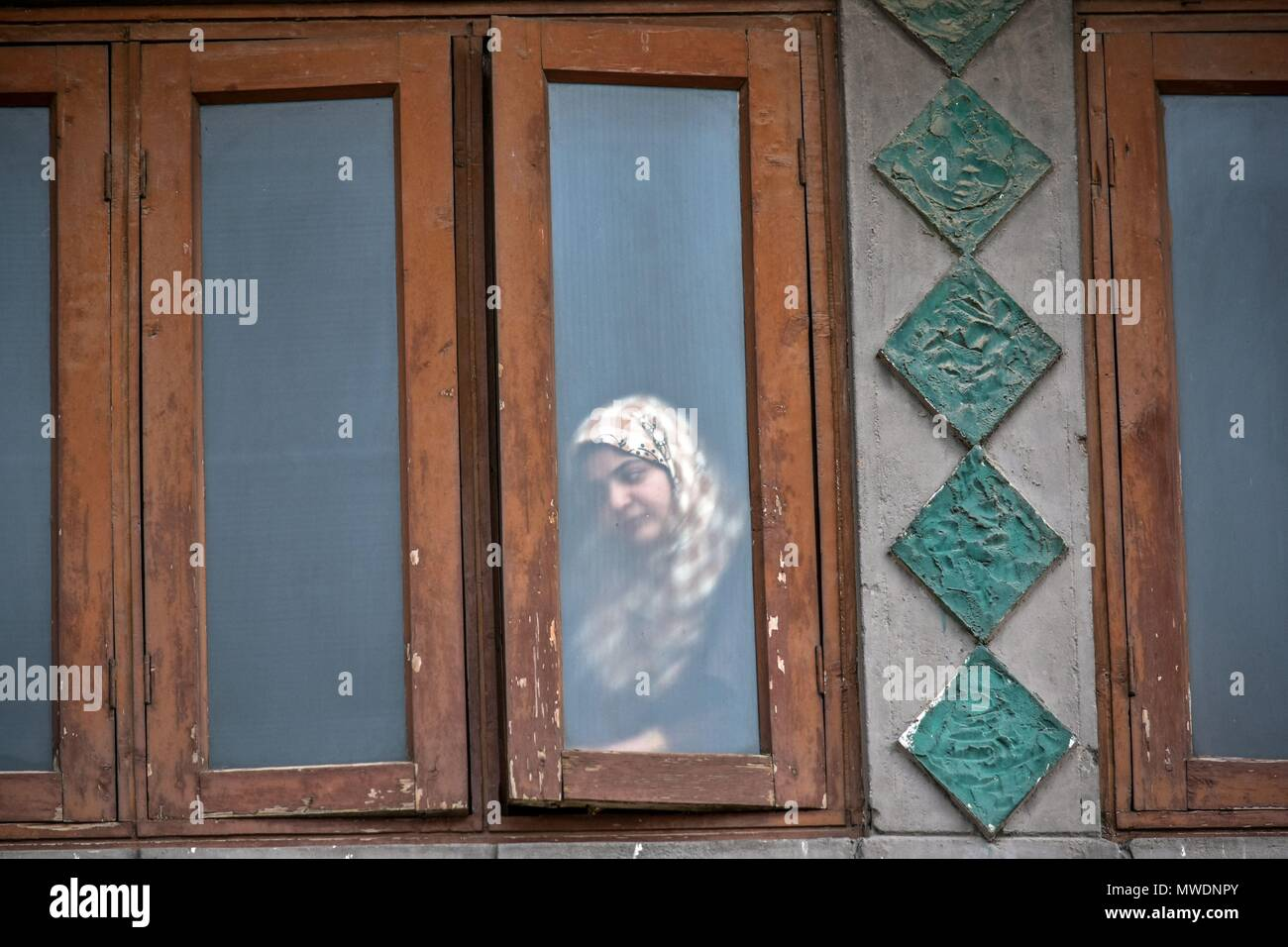 A Kashmiri woman looks out of her window as Indian government forces