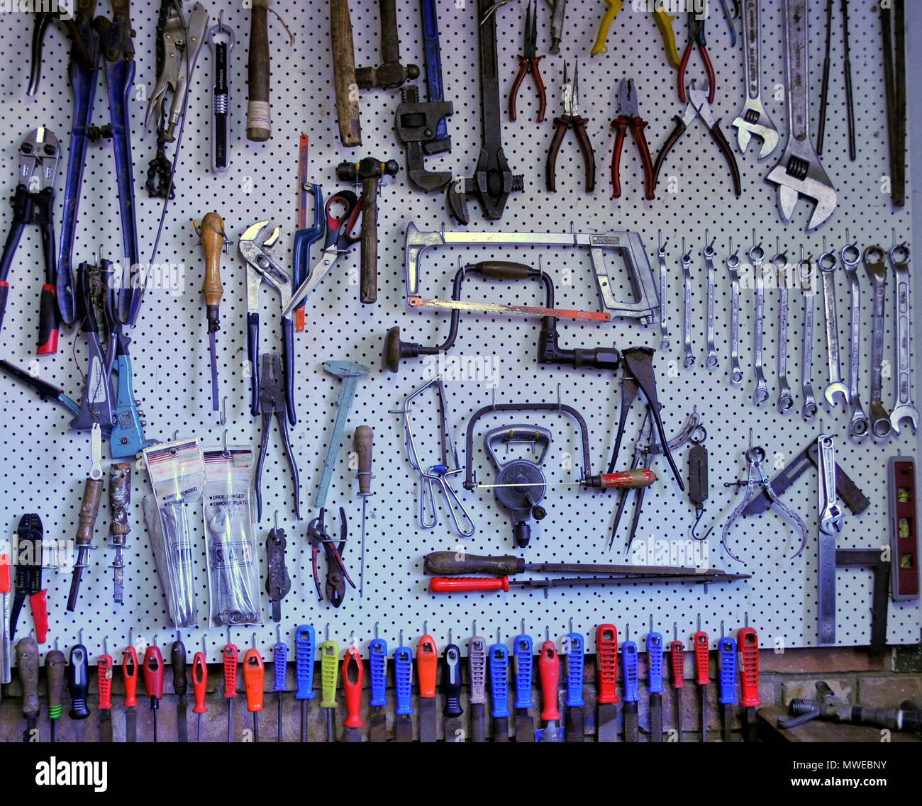 Hand tools organised for easy access on a peg board - Stock Image