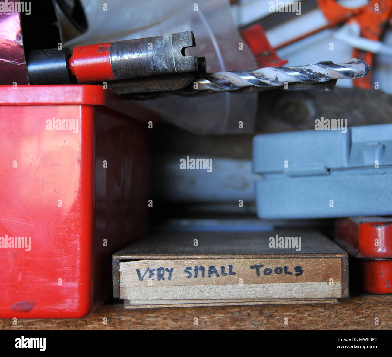 Tools on a shelf, with the smallest labelled and collected into a handy box - Stock Image