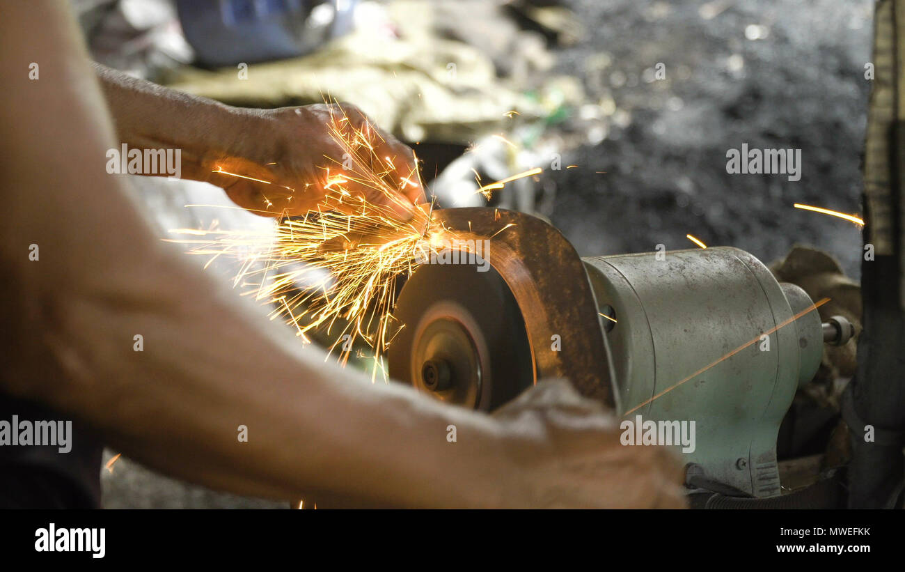 Sharpening the machete on sharpening machine in the smithy. Knife sharpener and hand with blade. Worker sharpening machete with grindstone abrasive disc cutter machine. - Stock Image