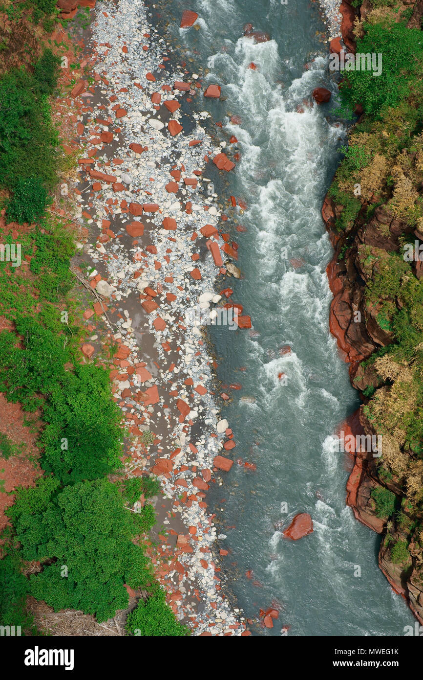 LARGE RED BOULDERS SCATTERED ON THE RIVERBED OF THE VAR RIVER (vertical aerial view from cliff with a 6-meter mast). Gorges de Daluis, France. - Stock Image
