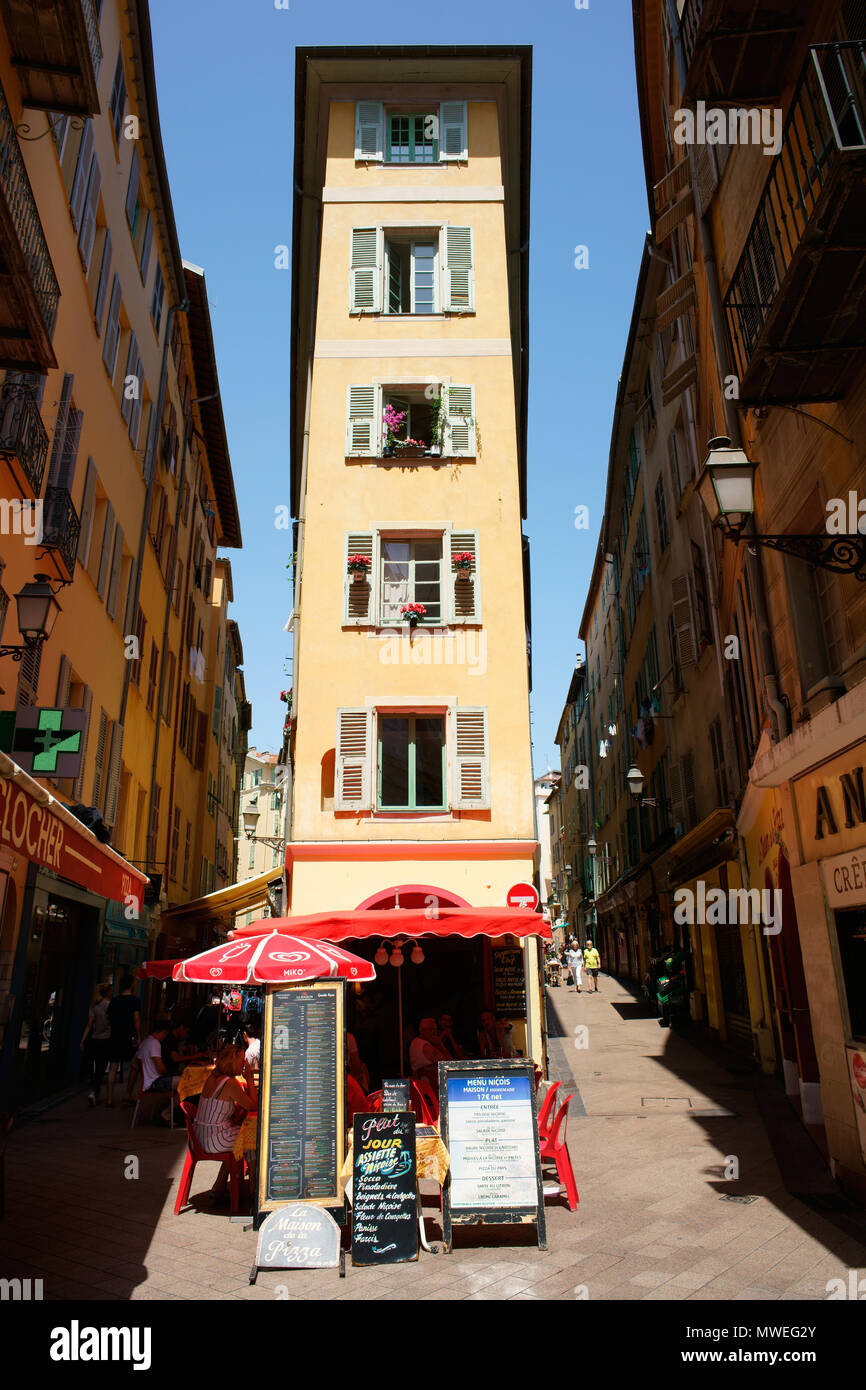 VERY NARROW BUILDING BETWEEN TWO NARROW STREETS. Old town of Nice, French Riviera, France. - Stock Image