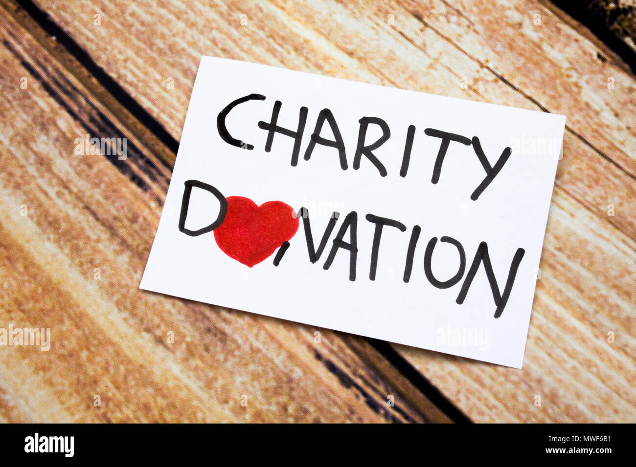 Conceptual image with Charity Donations handwritten message on the white paper with wooden background. Health and god will concept with red heart. Help for people having no money. - Stock Image