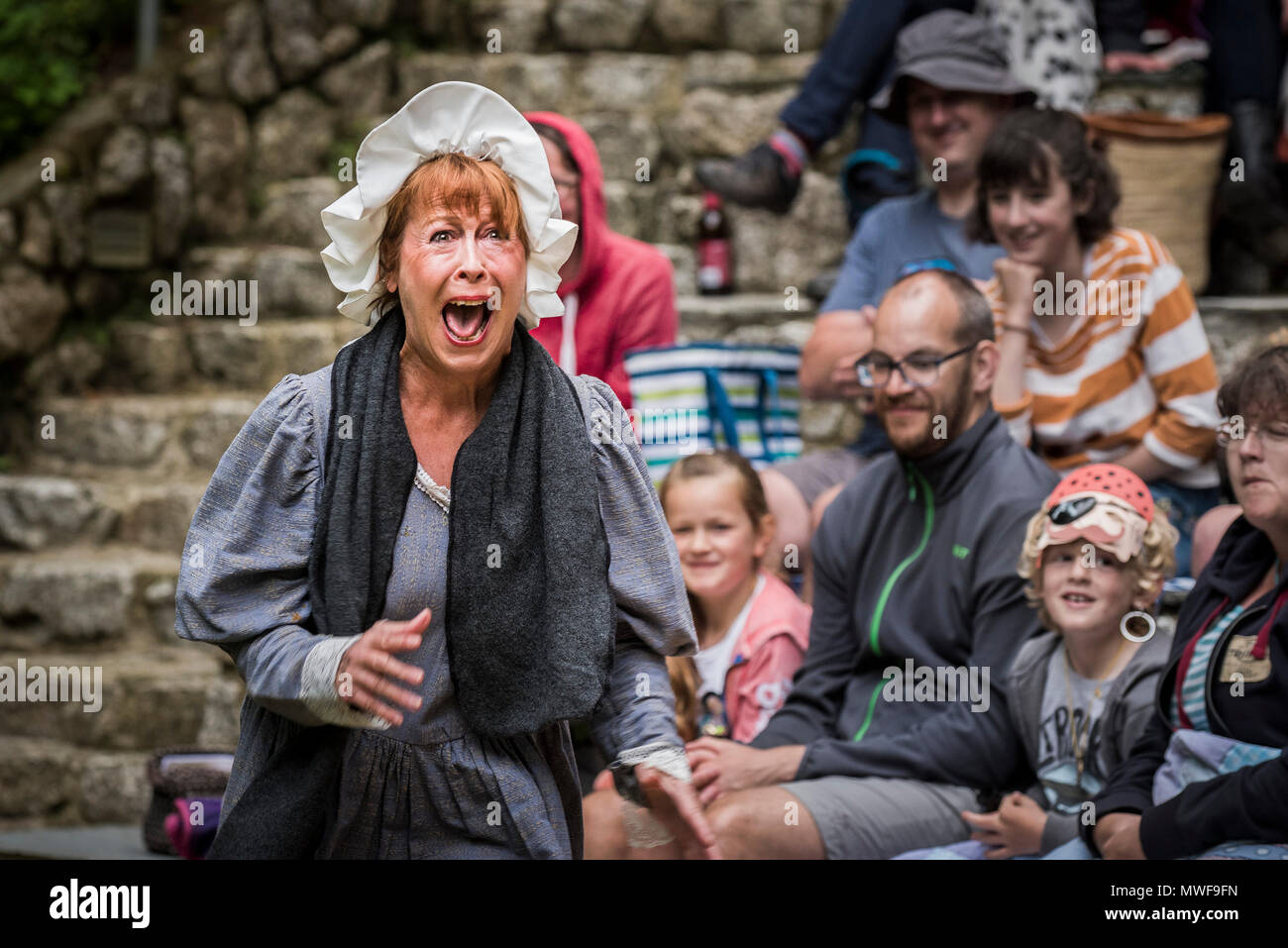Acting - An amateur drama group in a performance at Trebah Garden Amphitheatre in Cornwall. Stock Photo