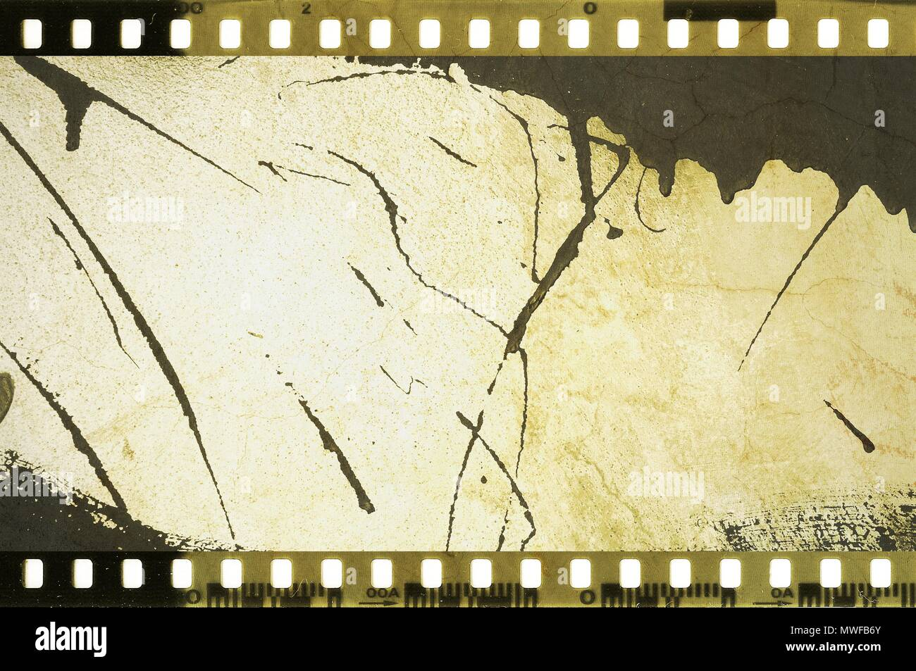 Grunge dripping cracked film strip frame in sepia tones. Damaged wall surface. - Stock Image