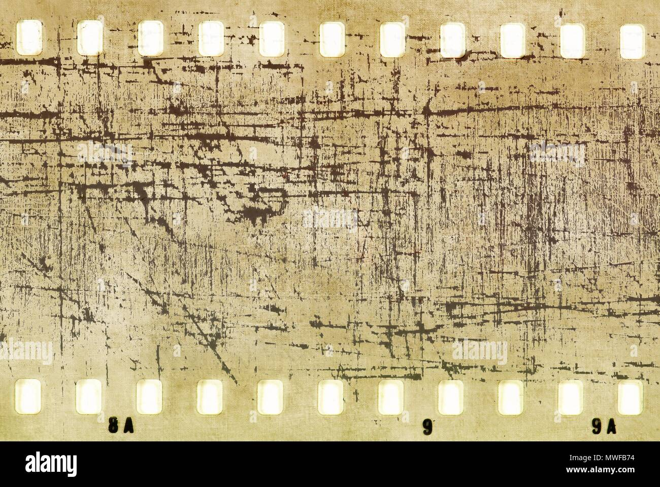 Vintage scratched film strip frame in sepia tones with copy space. - Stock Image