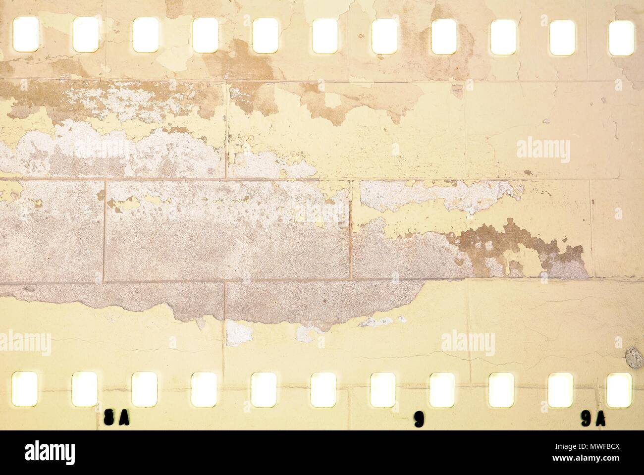 Grunge dripping cracked film strip frame in sepia tones. Damaged brick wall surface. - Stock Image