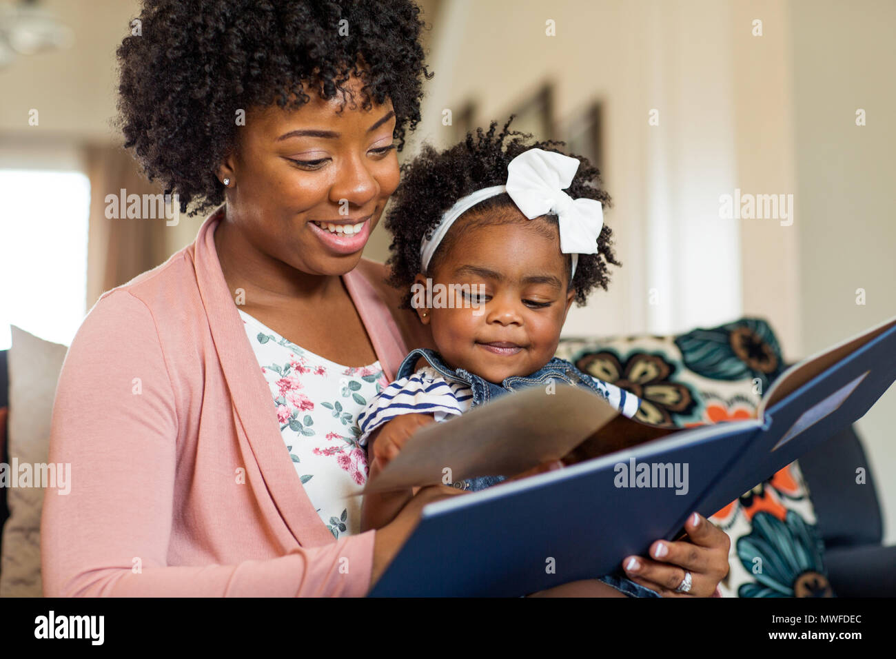 Mother reading a book to her little girl. - Stock Image