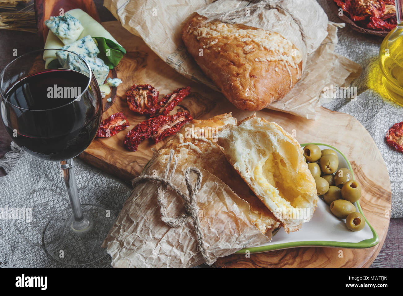 A glass of dry red wine and Italian Focaccia bread with cheese and a cheese platter with figs and Gorgonzola, brie, DorBlu and grapes. Selective focus - Stock Image