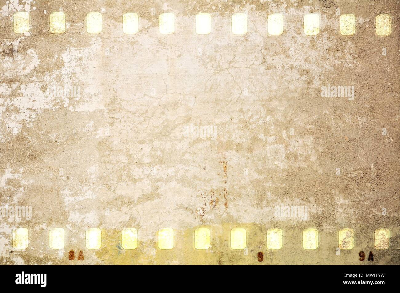 Grunge dripping cracked film strip frame in sepia tones. Wall surface. - Stock Image