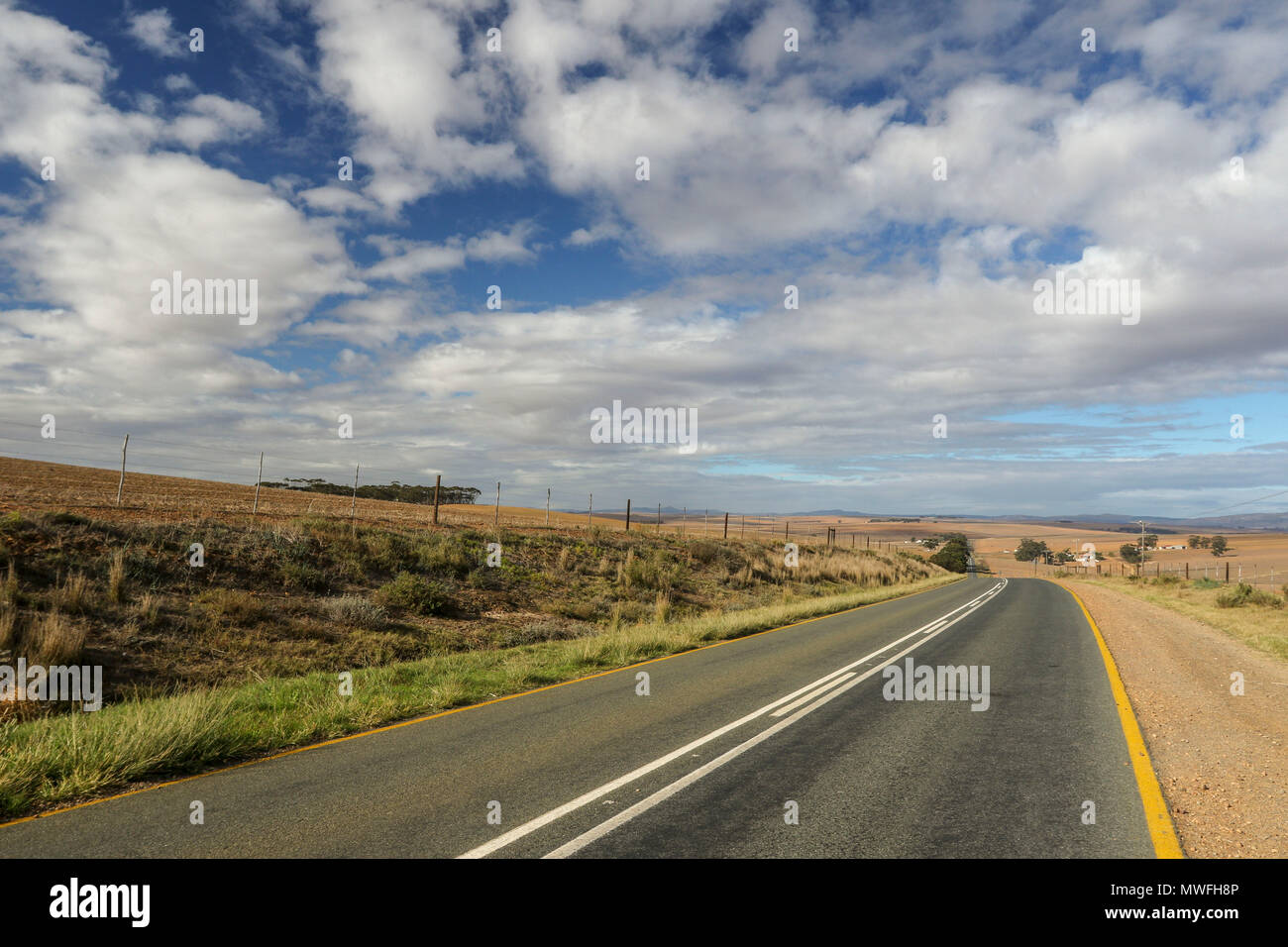 Receding road markings in the landscape with dramatic clouds and sunshine. Garden route, south africa Stock Photo