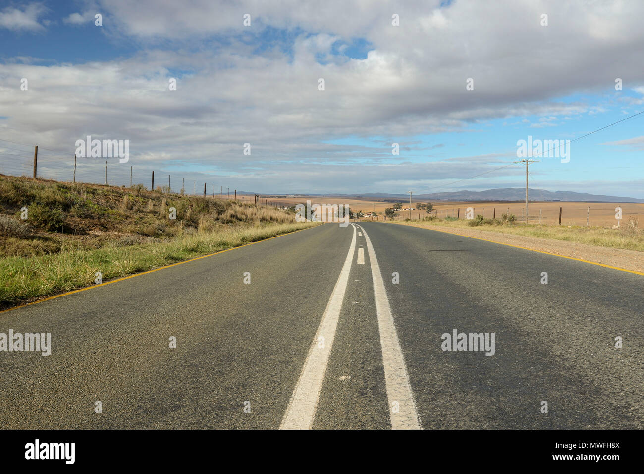 Receding road lane markings in the landscape, garden route, south africa - Stock Image