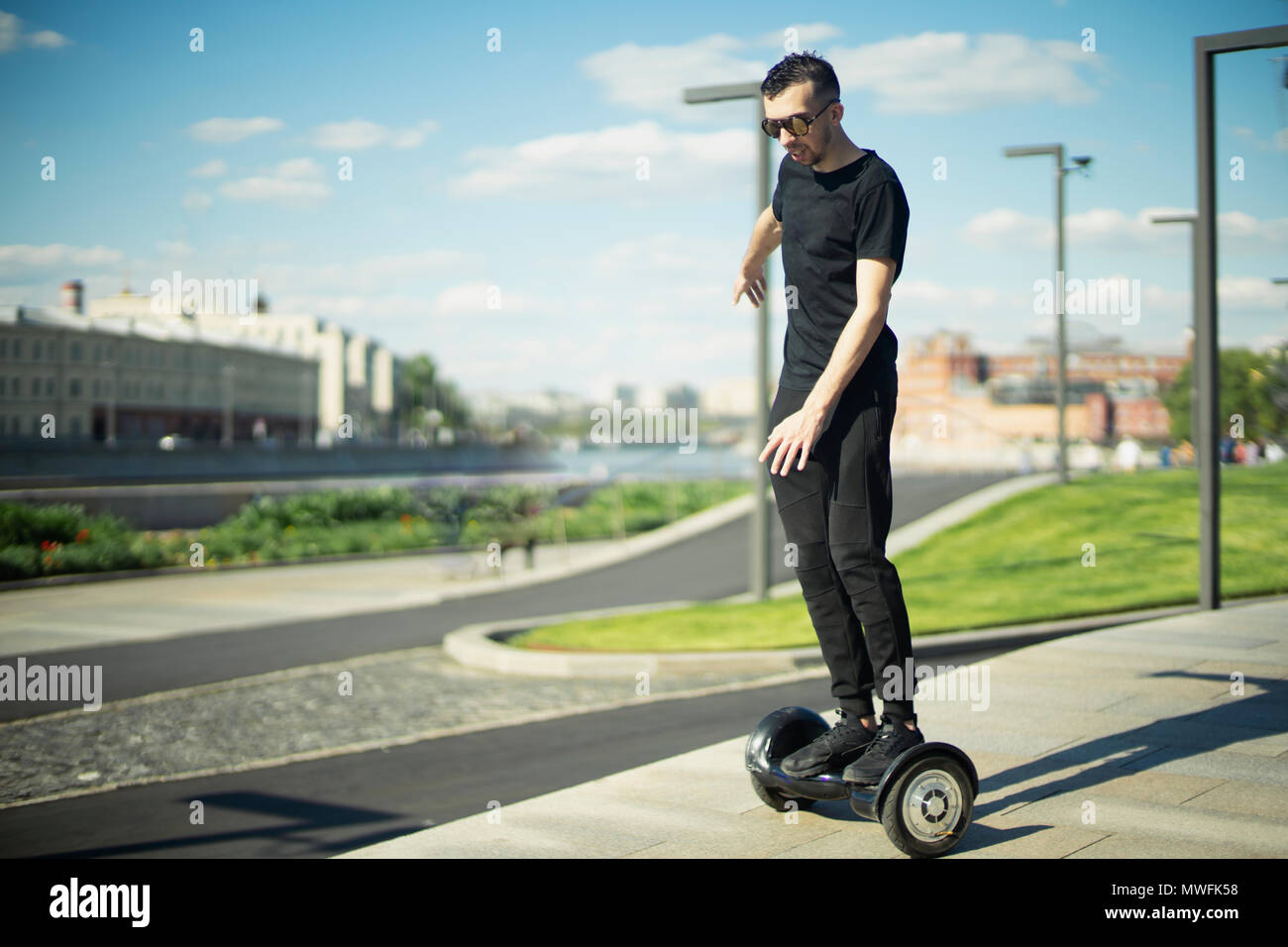Young brunette man rides a gyroscope at park. Man is on focus, background is blurred. - Stock Image