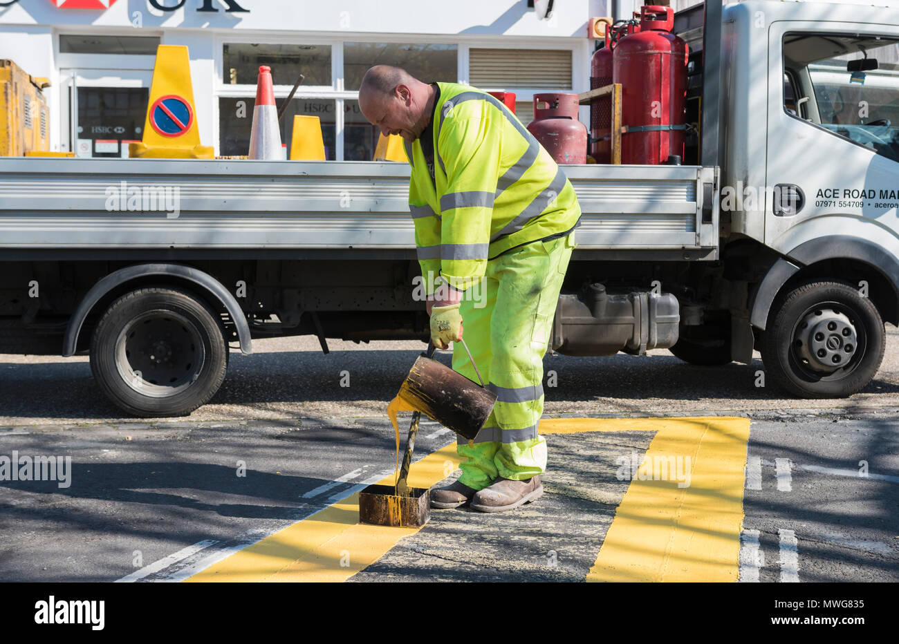 Worker painting yellow line on a road in England, UK. Road line painter. - Stock Image