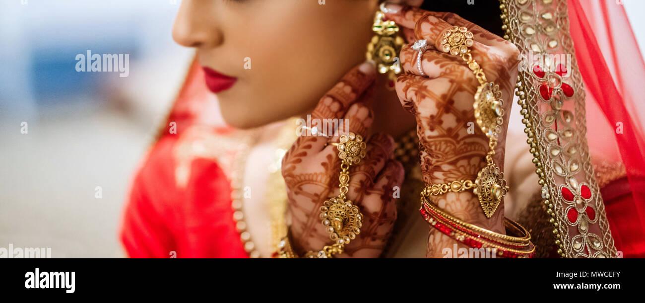 Pakistani bride putting earrings - Stock Image