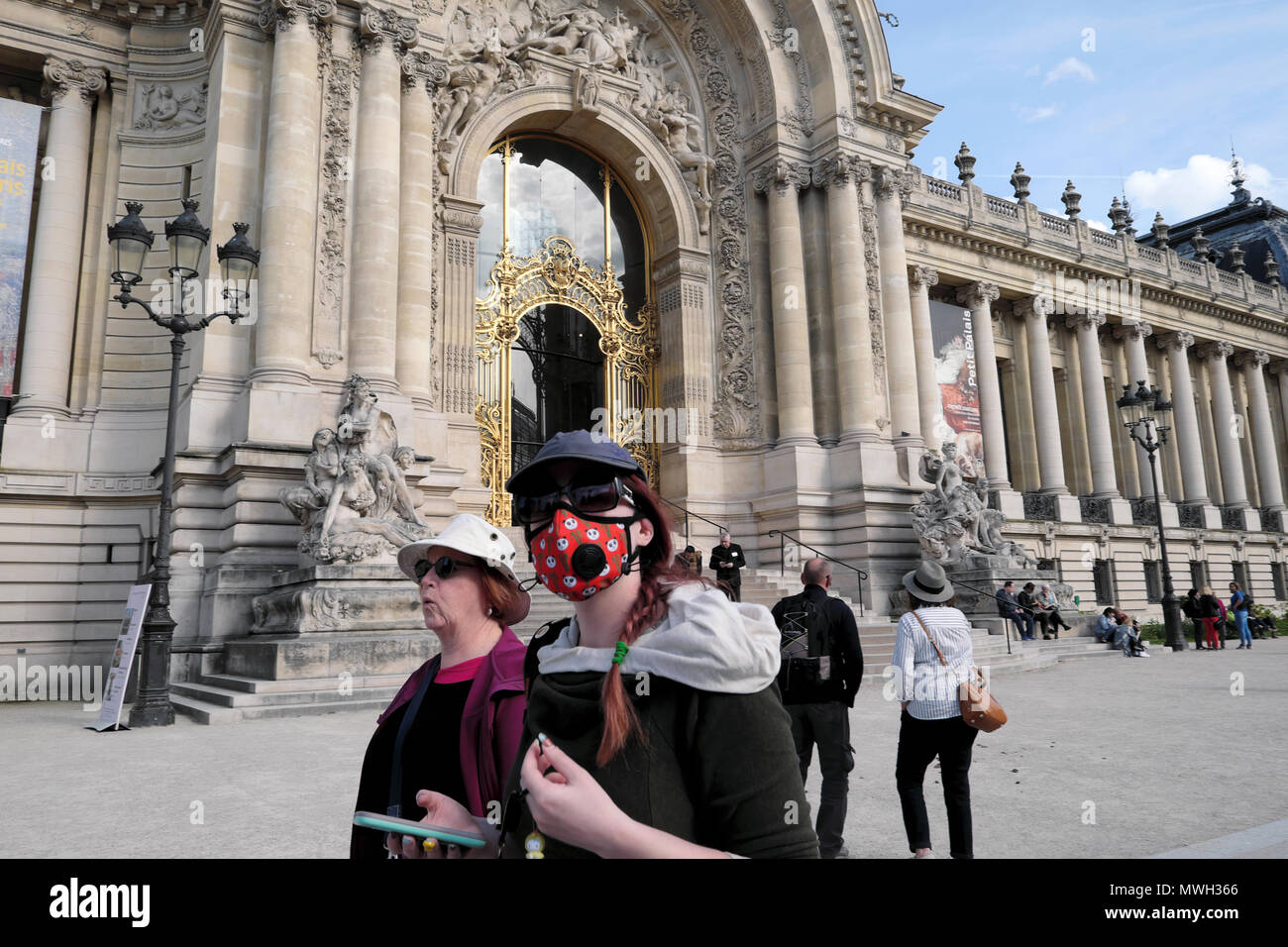 A woman wearing a respiratory mask walking outside the Petit Palais museum building in the street in Paris France    KATHY DEWITT - Stock Image
