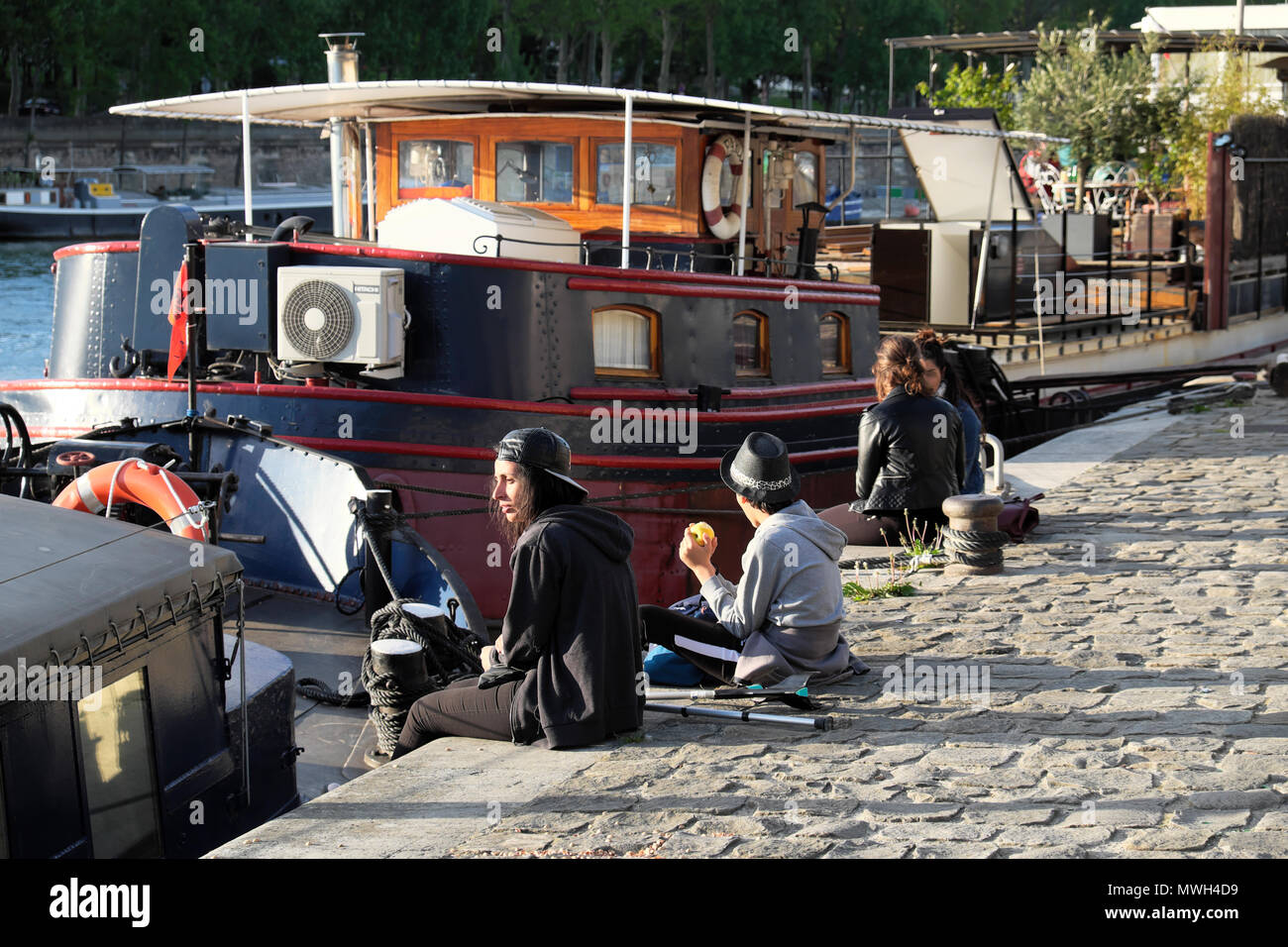 People sitting on a cobblestone quai by boats on the Left Bank along the River Seine on a spring afternoon in April Paris, France   KATHY DEWITT - Stock Image