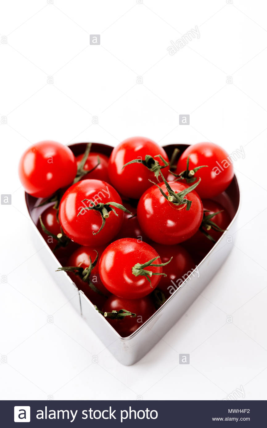 fresh tomatoes in a heart shape representing love and valentines day images - Stock Image