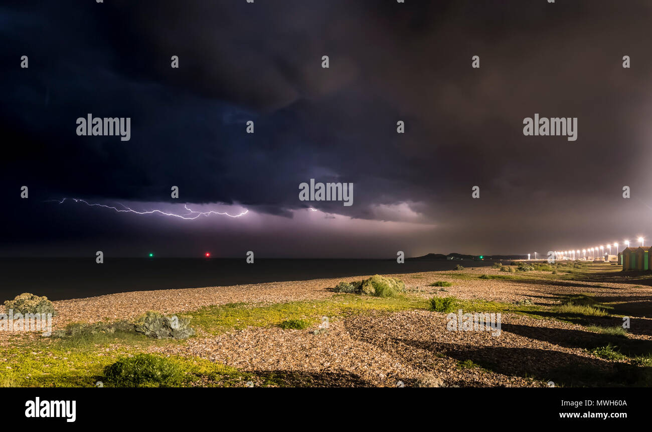 Dark black clouds with horizontal lightning as a thunder storm rages out at sea at night off the South Coast in the UK. Storm at sea. - Stock Image