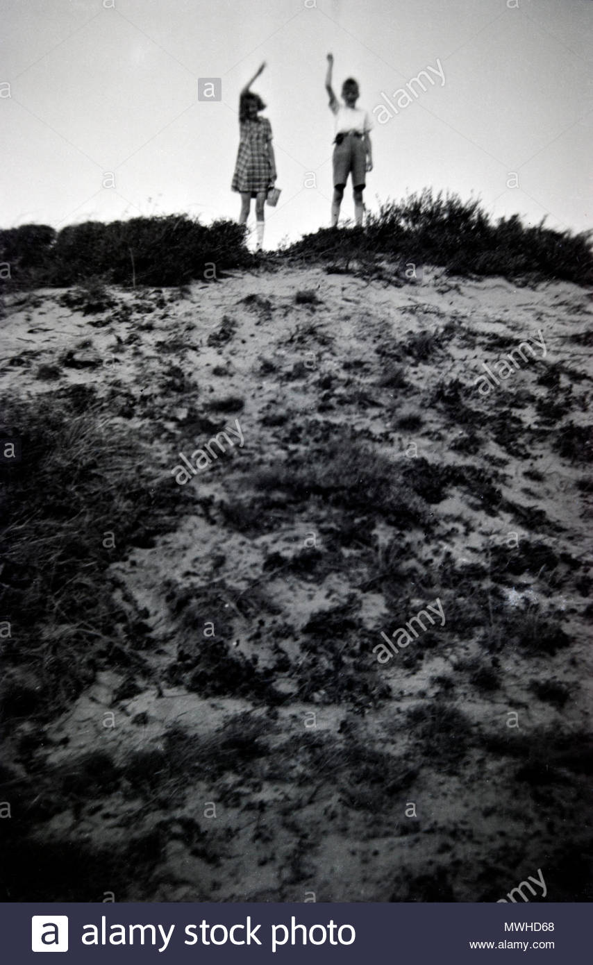 two children standing on top of a dune and waving 1950s Netherlands - Stock Image