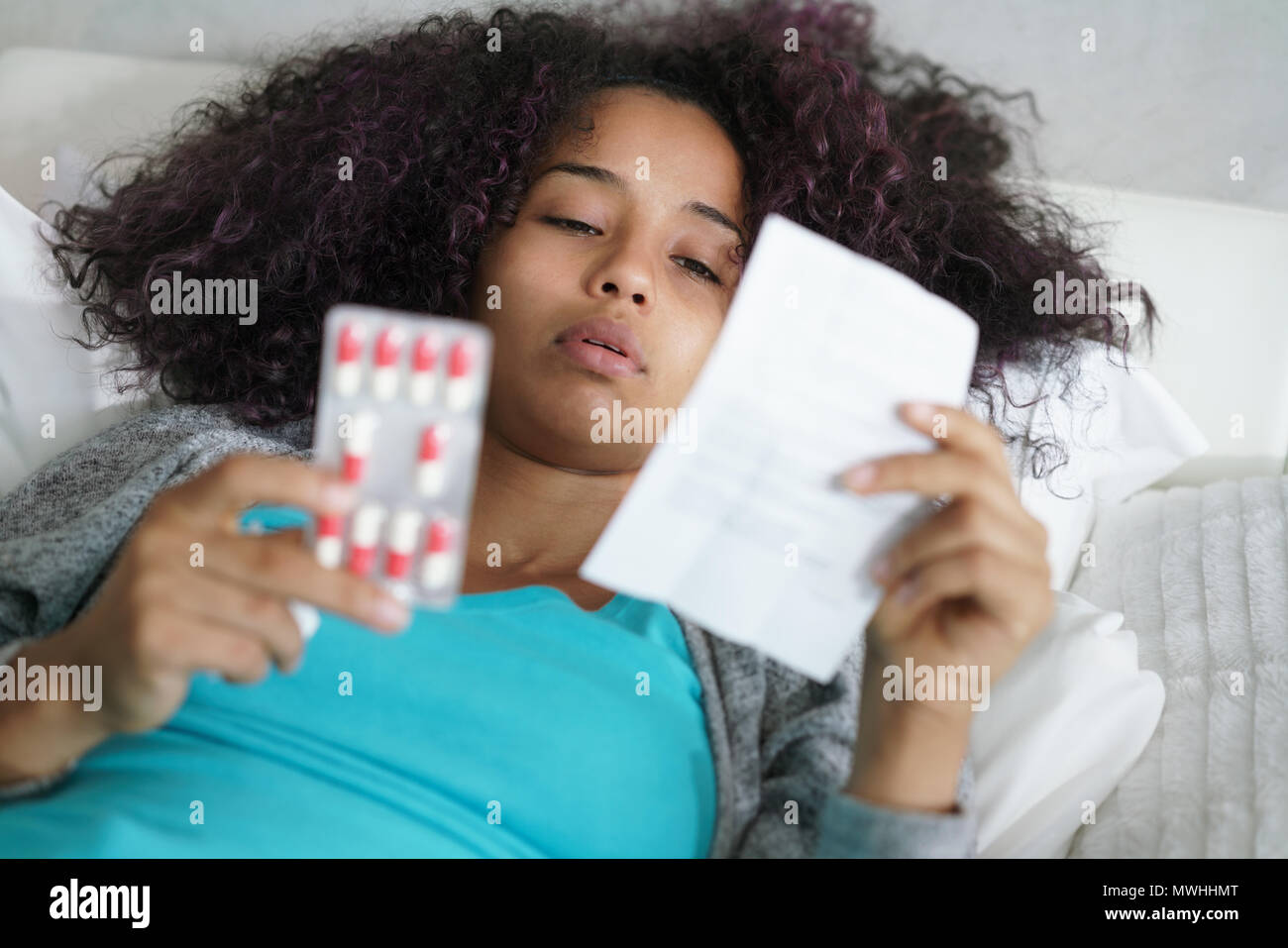 Sick african american girl with flu virus in bed at home. Ill young black woman with cold reading antibiotics prescription for illness. - Stock Image