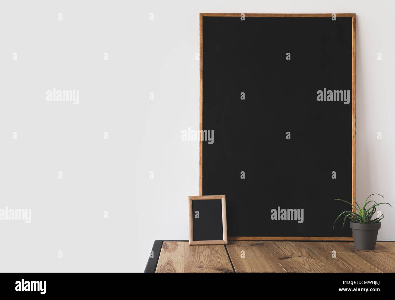 different blackboards and potted plant on wooden table on white - Stock Image