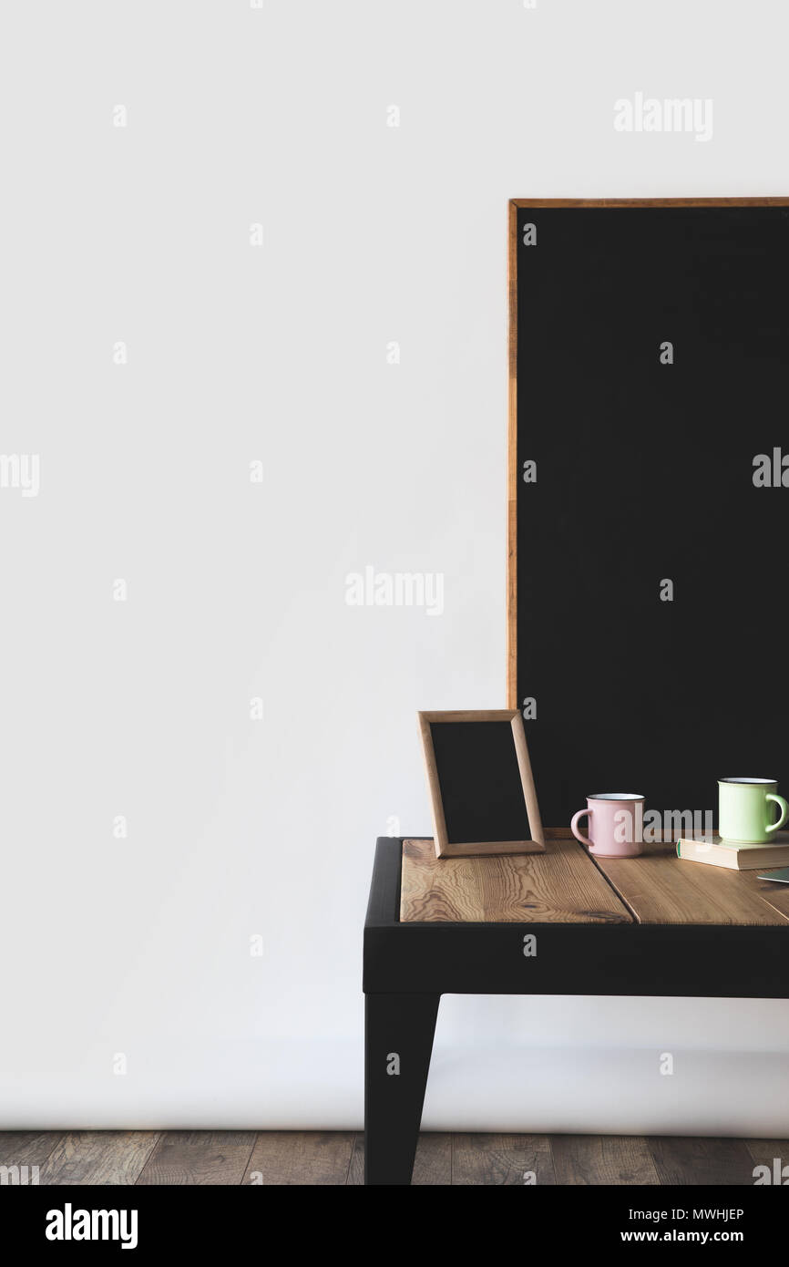 empty blackboards in frames with cups and book on white - Stock Image