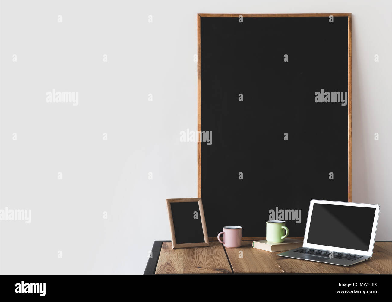 empty blackboards in frames with cups and laptop on white - Stock Image