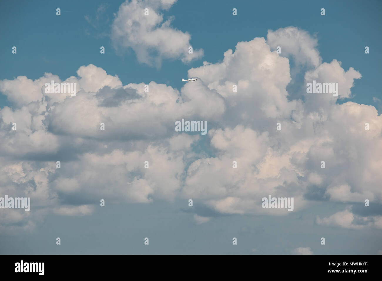 Little plane approaching into the blue Germany sky with white clouds - Stock Image