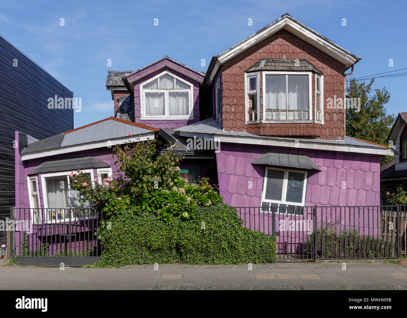 Dalcahue, Chiloé, Chile, 2018: A house shingled with tejuelas, first floor raked to unusual angle. - Stock Image
