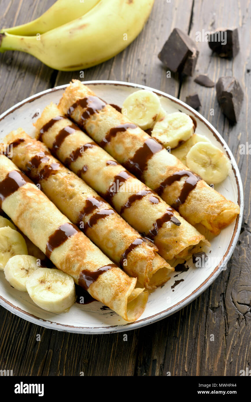 Delicious crepe roll with banana slices on wooden table. Thin pancakes, crepes with chocolate sauce. - Stock Image