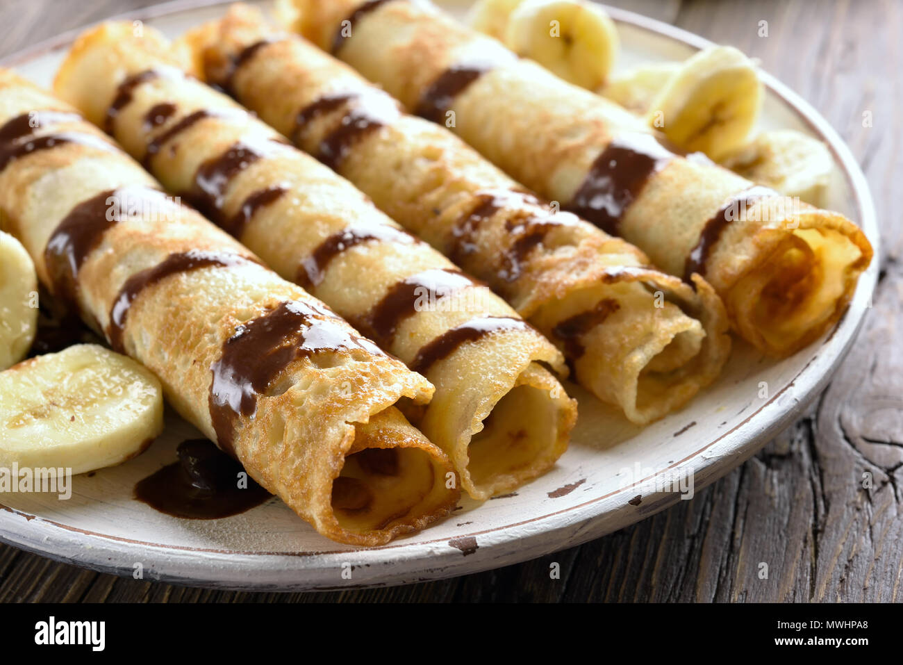 Close up of tasty crepe roll with banana slices on wooden table. Thin pancakes, crepes with chocolate sauce. Shallow depth of field - Stock Image