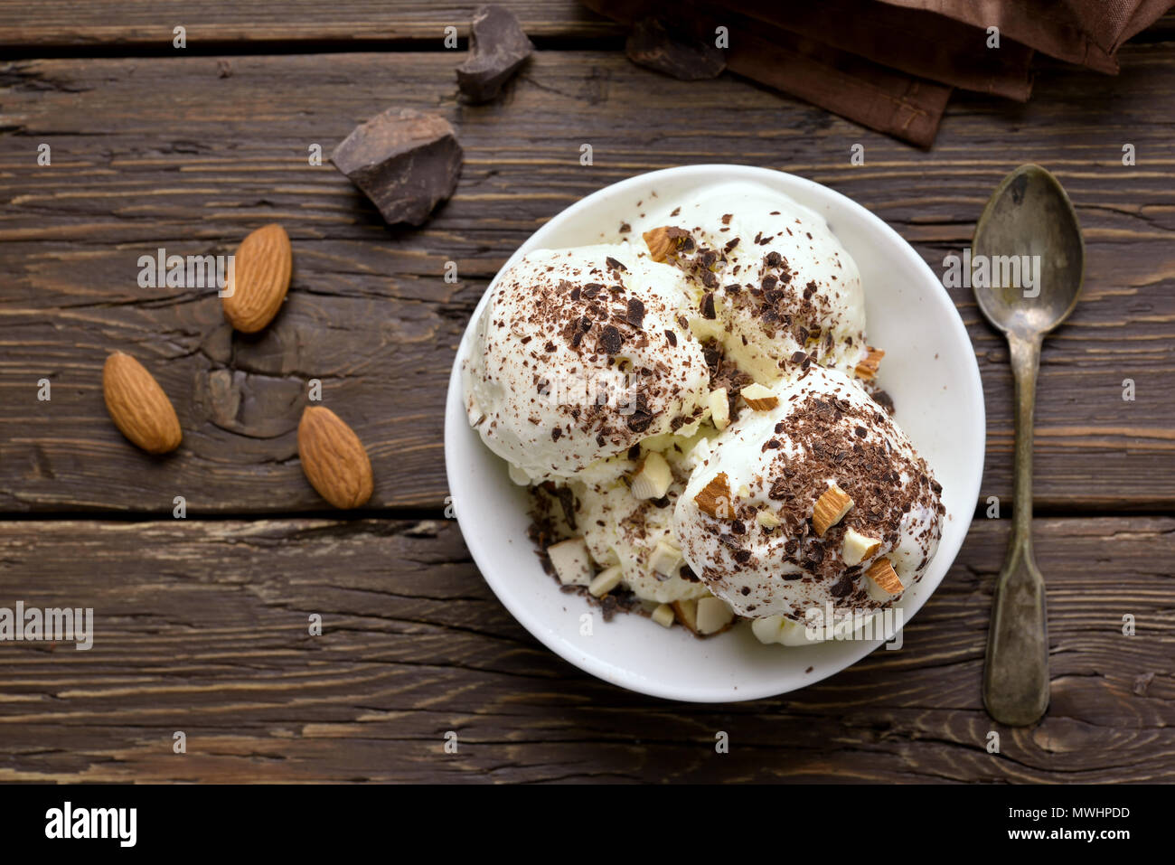 Vanilla ice cream with nuts in bowl on wooden background. Cold summer dessert. Top view, flat lay - Stock Image