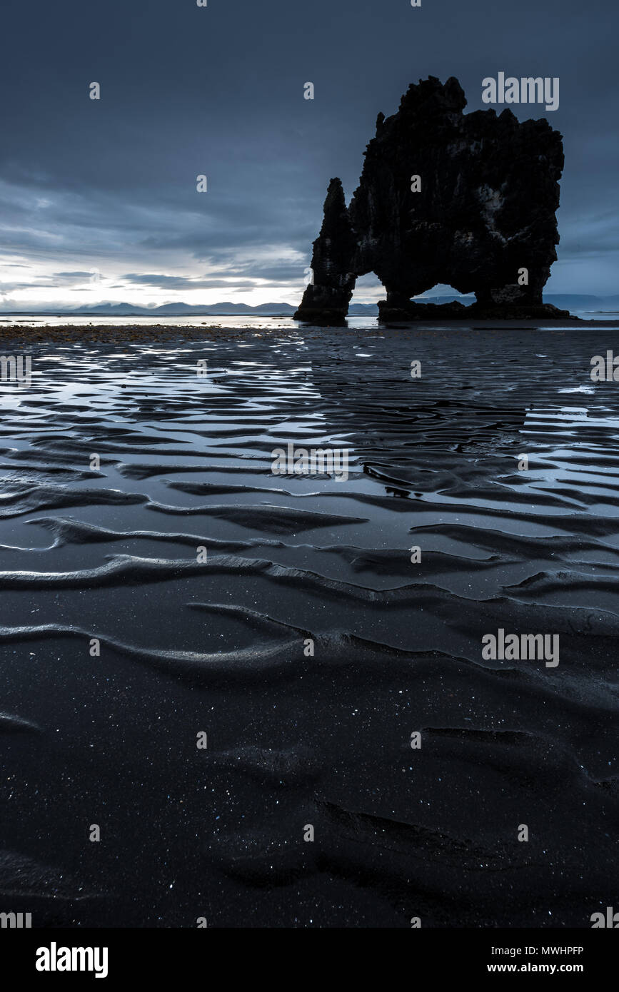 located on the North Shore of Iceland Hvitserkur is a truly iconic landmark. there is a seal colony nearby and a creek is running down the steep slope - Stock Image