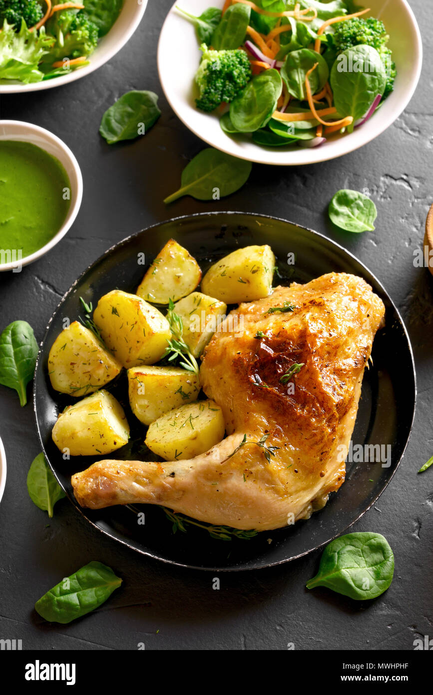 Tasty fried chicken leg with potato. Dish for dinner on black stone background. Top view - Stock Image