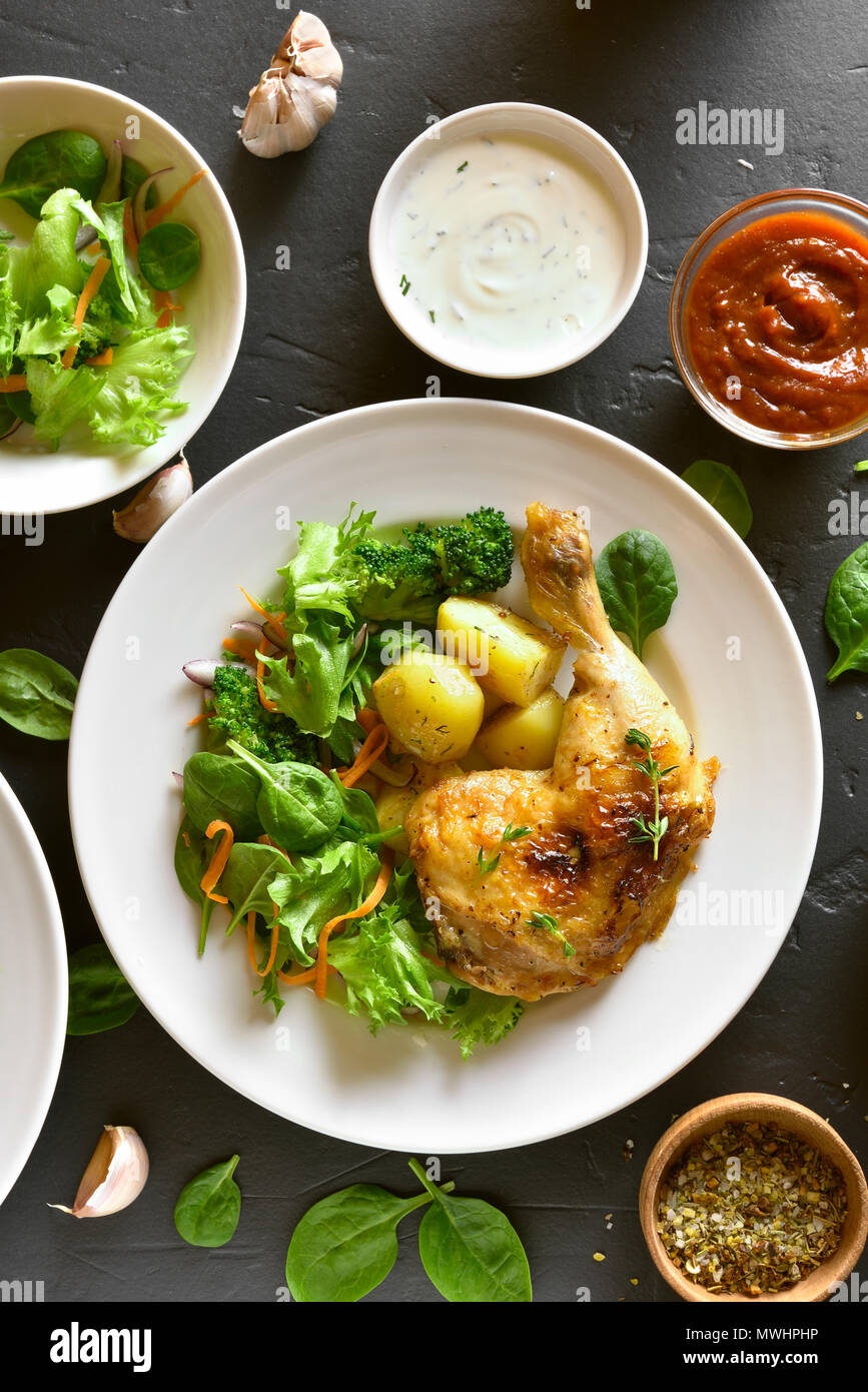 Fried chicken leg with potato and green salad on black stone background. Top view, flat lay - Stock Image