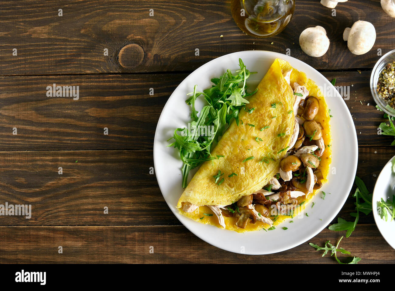 Omelette stuffed with mushrooms, pieces of chicken meat, greens on wooden background with copy space. Top view, flat lay - Stock Image