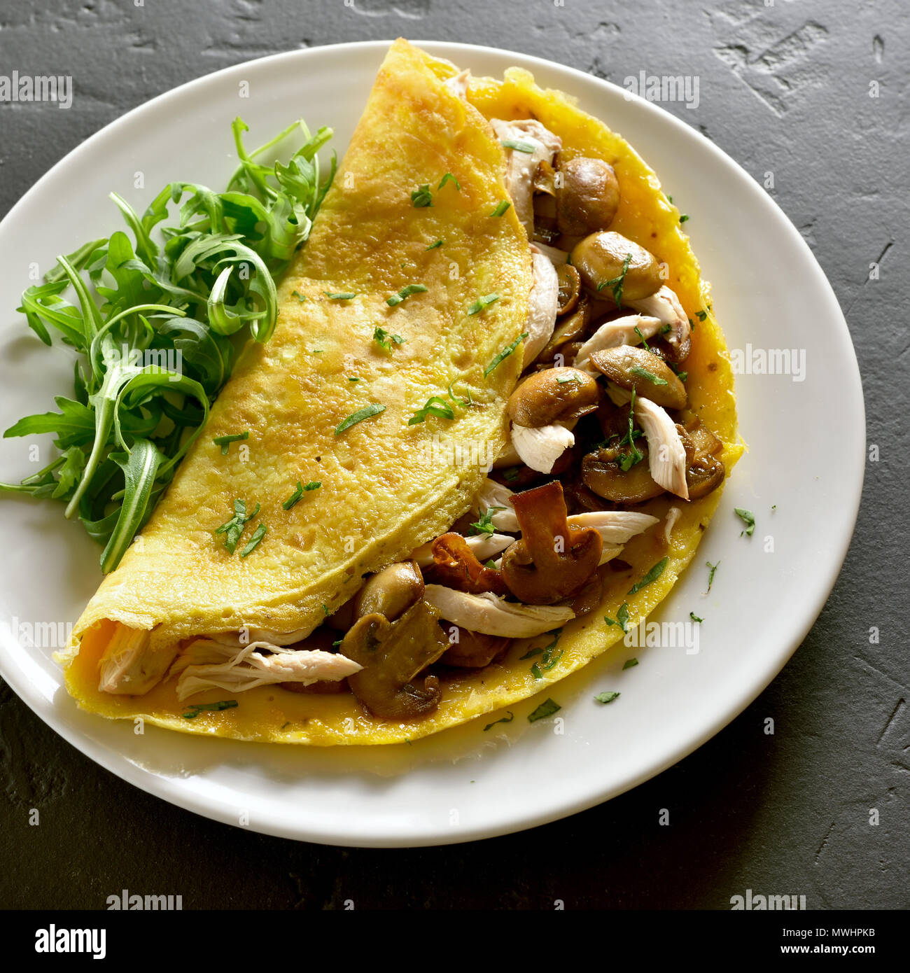 Close up of omelet stuffed with mushrooms, chicken meat, greens on black stone table. - Stock Image
